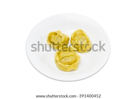 Three boiled manti (dumplings, meat dumplings) on a white dish on a light background