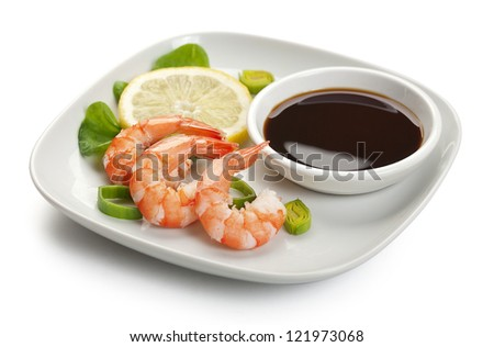 Three boiled shrimp's tails with leek, lettuce, lemon and soy sausage on the white plate
