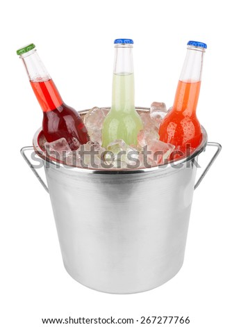 Three bottles in bucket filled with ice isolated on white - stock photo
