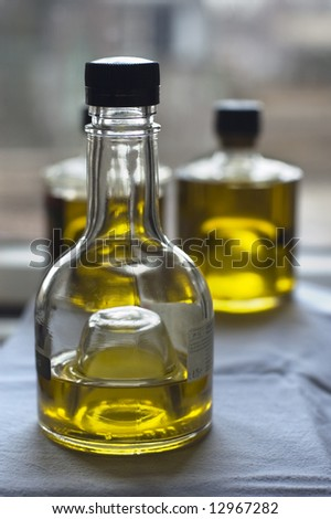 Three bottles of olive oil at the window - stock photo