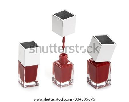 three bottles of red nail polish on white background - stock photo