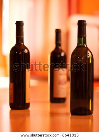 Three bottles of wine on the floor of a bright room (only one in focus, smooth soft image) - stock photo