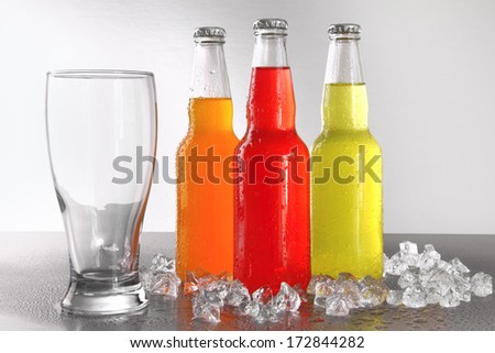 Three bottles with drinks with glass and ice against silver background - stock photo