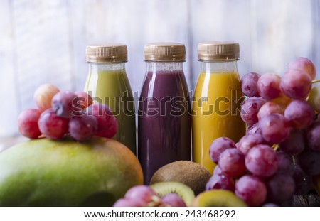 Three bottles with smoothies and fresh fruit (mango, grapes, apple) - stock photo