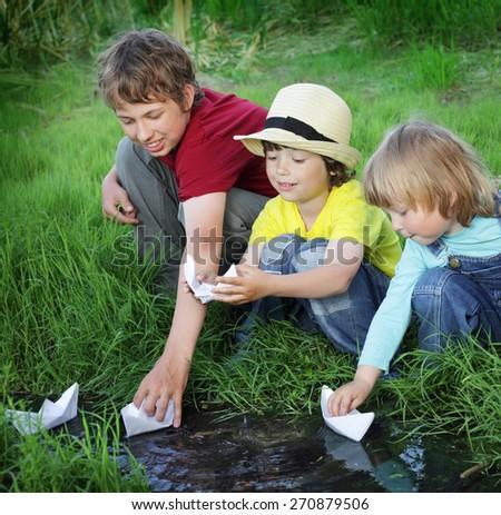 three boy play in  stream - stock photo