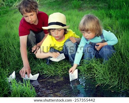 three boy play in stream summer day - stock photo