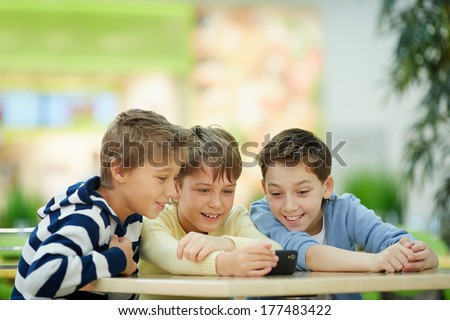 Three boys absorbed in smartphone screen - stock photo