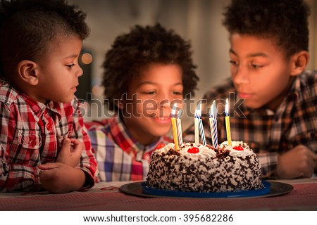 Three boys and birthday cake. Afro kids at birthday table. Festive date to celebrate. Surprise for our brother. - stock photo