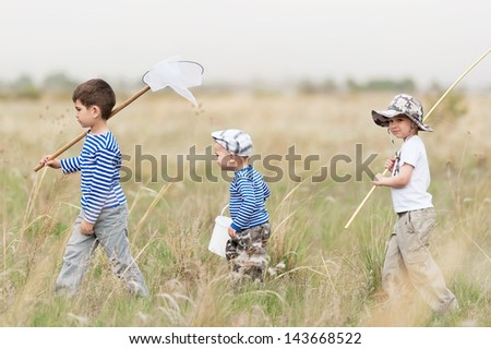 Three boys - fishermen on a meadow at the catch - stock photo