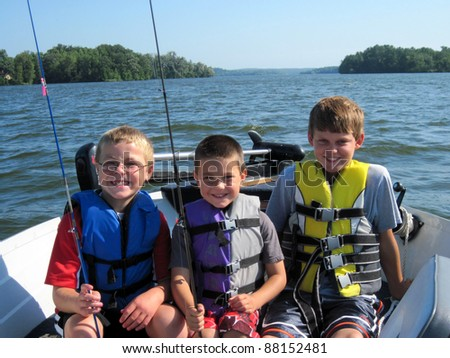 three boys in life jackets fishing on a lake - stock photo