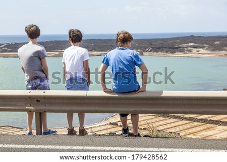 three boys leaning at guide rail and look at the scenic landscape
