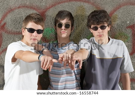 Three boys showing something in front of their glasses - stock photo