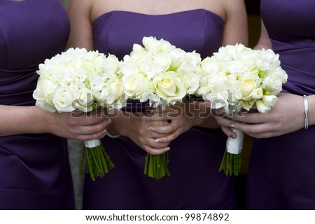 three bridesmaids holding wedding bouquets - stock photo
