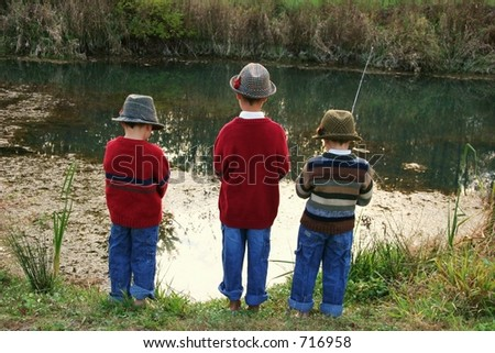 Three brothers fishing on the riverbank wearing grandfather's hats. - stock photo