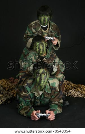 Three brothers in camo paint and fatigues playing video games. - stock photo
