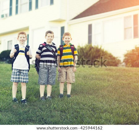 Three brothers outside their house going to school - stock photo