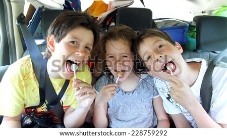 three brothers while traveling by car while eating a candy - stock photo