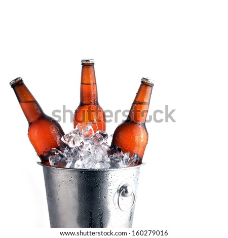 Three brown beer bottles in ice bucket with condensation  - stock photo