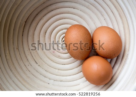 Three brown country eggs in a white bowl from above.