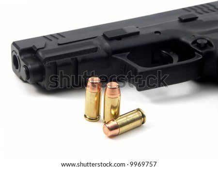 three bullets and gun on the white background - stock photo