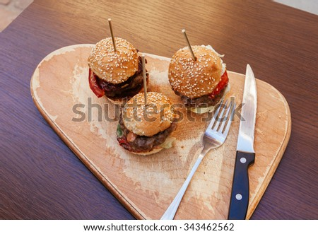 Three Burgers Sliders On Rustic Wooden Plate - stock photo