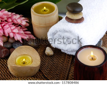Three burning candle ,tropical flower, towel on bamboo mat
