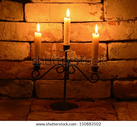 Three burning candles on the stone background in night - stock photo