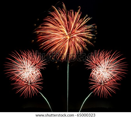 Three bursts of red white and gold fireworks against a black night background - stock photo