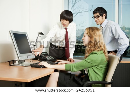 Three business colleagues analyzing data on computer screen - stock photo