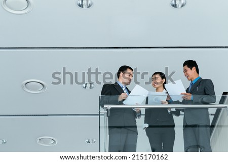 Three business colleagues discussing papers while standing on the balcony - stock photo