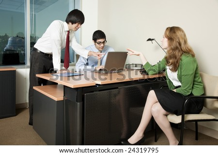 Three business colleagues in a meeting, discussing data. - stock photo