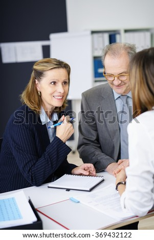Three business colleagues in a meeting with an over the shoulder view of a middle-aged experienced businesswoman with an alert interested expression