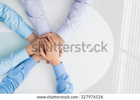 Three business colleagues showing their team spirit - stock photo