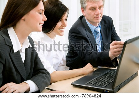 Three business colleagues sitting around table and working together, looking at monitor - stock photo