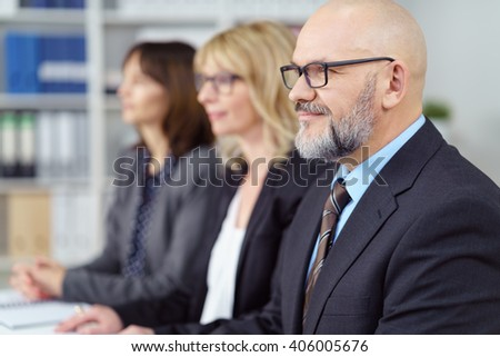 Three business executives in a management meeting sitting together at a table listening to a presentation with focus to a bald middle-aged man in the foreground with a quiet smile - stock photo
