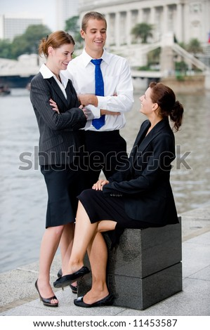 Three business executives outside by a river in the city