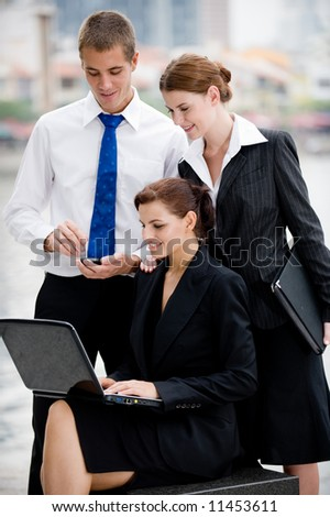 Three business executives with laptop outside by a river in the City - stock photo