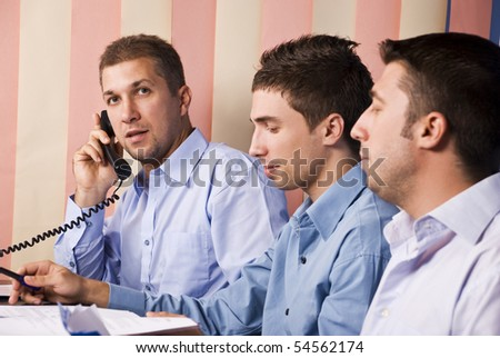 Three business men partners working in office,focus on last men that speaks by phone , the others reading some paperwork