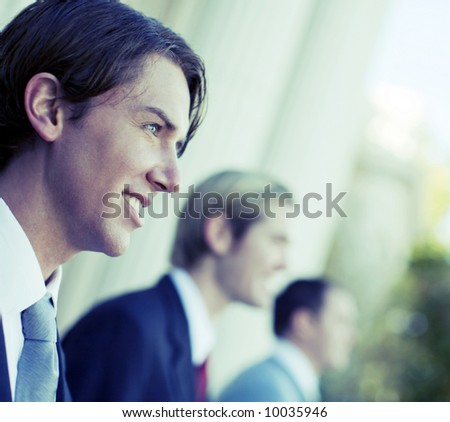three business men standing and smiling in same direction - stock photo