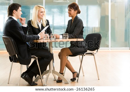 Three business partners discussing important affairs at working meeting - stock photo