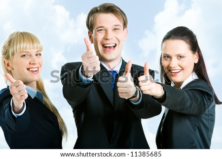 Three business partners holding their thumbs up - stock photo
