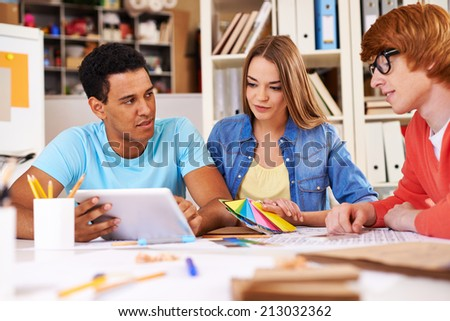 Three business partners in casual voicing their ideas at meeting - stock photo