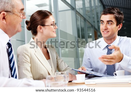 Three business partners sitting in office and interacting at meeting - stock photo
