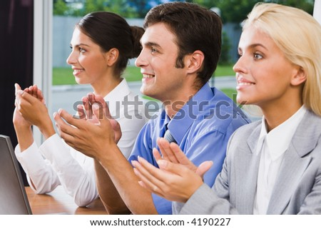 Three business people applauding after finish of speech at a seminar - stock photo