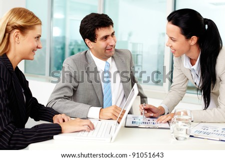 Three business people discussing ideas at workplace in office - stock photo