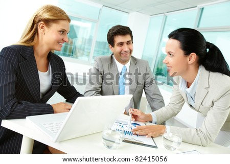 Three business people discussing papers at workplace in office - stock photo