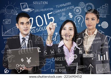Three business people discussing the resolutions in 2015 - stock photo
