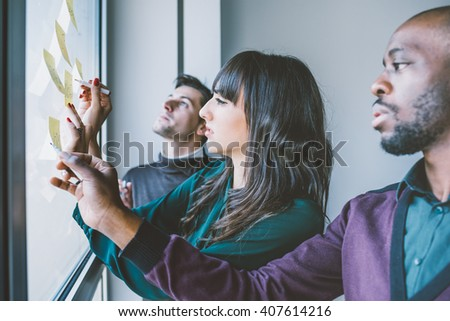 Three business people having a meeting in office. They are standing in front of glass wall with post it notes, pointing and discussing - business, teamwork, brainstorming concept