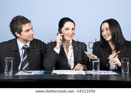 Three business people having a meeting,the middle businesswoman speaking at phone mobile and the other two people having an conversation and laughing together - stock photo