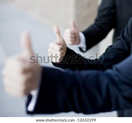 Three business people in suits giving thumbs up - stock photo